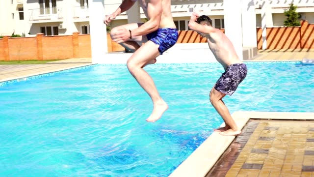 Two young athletic men in swimshorts running and jumping to the swimming pool turning around. Slowmotion shot. video