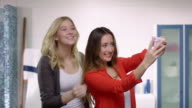 Two young beautiful woman doing poses and taking pictures with a mobile in a modern bathroom with a lot of fun video