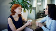 Two young beautiful women talk over cup of coffee in office video