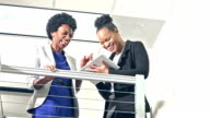 Two young black businesswomen with tablet computer video