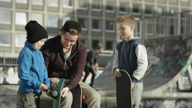 Two young boys and one adult reparing skateboard video