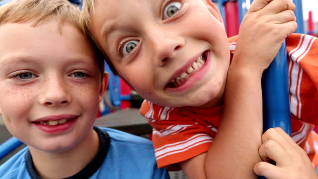 Two young boys at playground making silly faces video