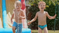 SLO MO Two young boys having fun with water sprinkler video