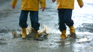 Two young boys jumping in mud puddle video