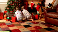 Two young boys run to gifts on Christmas morning video