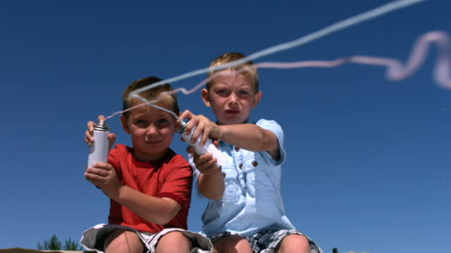 Two young boys shoot party string, slow motion video