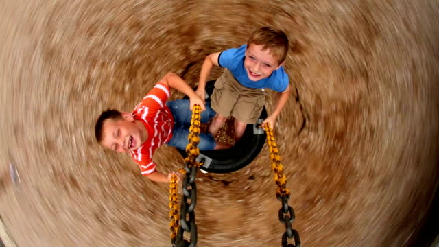 Two young boys spinning tire swing at school playground video