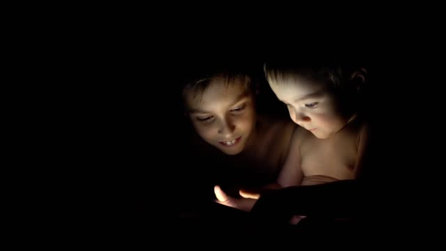 Two young brothers playing with tablet at night. 4K video