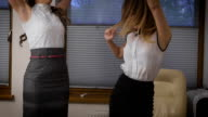 Two young business women have uspeha.Oni rejoicing and dancing in the office video