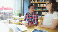 Two young businesspeople working on laptop in a coffee shop. video
