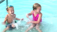 Two young children splashing each other in swimming pool video