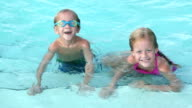 Two young children swimming in pool video