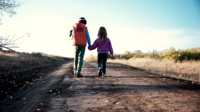 Two young children walking along a dirt road video