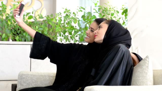 Two young Emirati women taking a selfie video