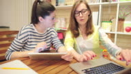 Two young female using laptop and digital tablet in a bookstore. video