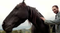 Two young friends, man and woman, smiles, strokes and hugs black horse outdoor - HD video footage video