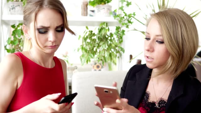 Two young girlfriends using smartphone and talking in cafe and drinking coffee. Shot in 4k video