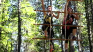 Two young girls climbing a rope ladder video