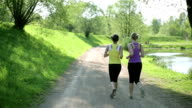 Two young girls jogging in the park, slow motion video