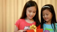 Two young girls opening Christmas gift video