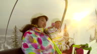 Two young girls riding chair lift at ski hill video