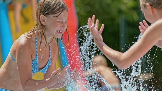 SLO MO TU Two young girls splashing water in the backyard video