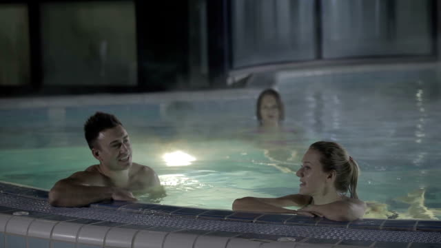 Two young guy and girl swimming in the pool and talking video