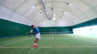 Two young guys playing tennis on court in slowmotion video