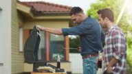 Two Young Handsome Men are Cooking Burgers on Grill and Communicating at Bright Summer Day. video