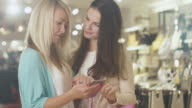 Two young happy girls are using a smartphone in a department store. video