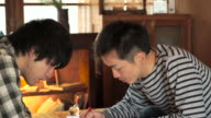 Two young Japanese men have to fill in something in a cafe video