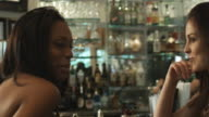 Two young ladies at the bar eyeing video