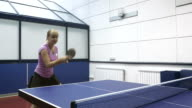Two young man and woman playing a ping-pong at the court video