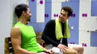 Two young man having conversation in the gym's locker room video