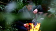 MS Two young men drinking coffee near campfire video