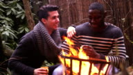 MS Two young men enjoying coffee cup near campfire video