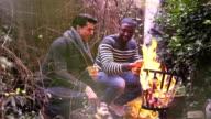 MS Two young men enjoying coffee near campfire video