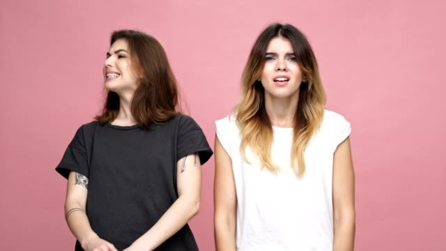 Two young outraged women standing with arms folded and looking at camera isolated over pink background video