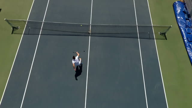 Two young people play tennis at the tennis court outdoors video