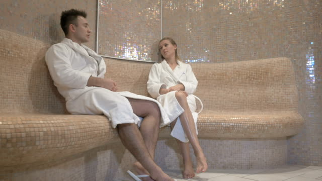 Two young people relax on marble bench video