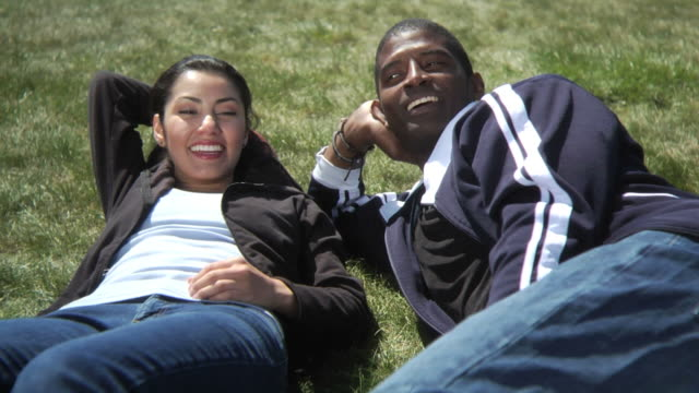 Two young people relaxing in grass video