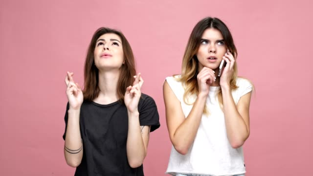 Two young pretty girls standing with mobile phone isolated over pink background. One girl talking on mobile phone and the other one holding fingers crossed for good luck video