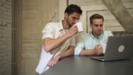 Two young professional men drinking coffee look to computer and talk video