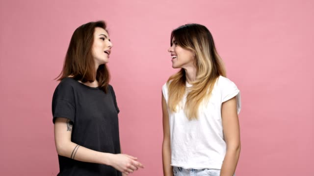 Two young smiling women greeting each other with kiss and showing displeasure isolated over pink background video