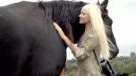 Two young smiling women in nature outdoor strokes and hugs black horse - slow-motion HD video footage video