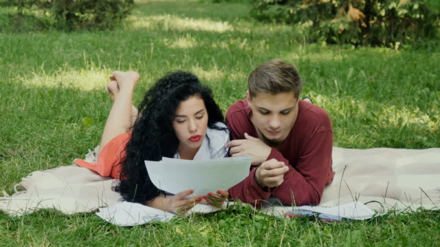 Two young students reading the synopses and prepares to exams in summer park video