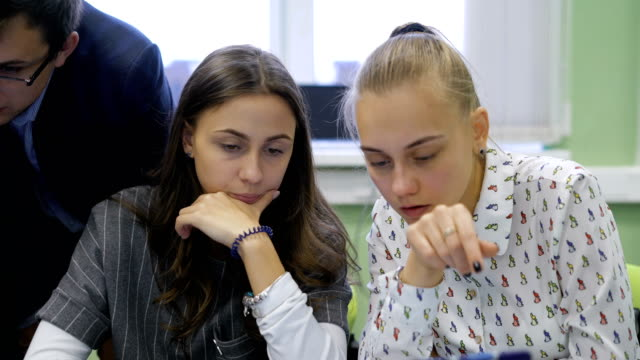 Two young students sitting at the table in the audience and discussing the task video