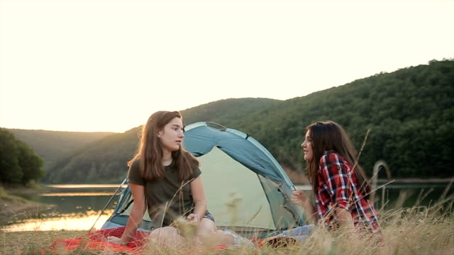 Two young teenage friends talking and smiling on the camp near the lake video