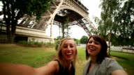 Two young tourist women taking selfie at Eiffel tower-Paris video