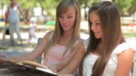Two young woman in summer outdoors sidewalk cafe video